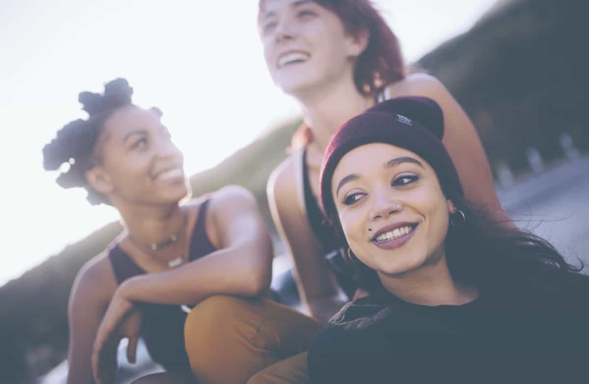 Group of mixed race grunge girls laughing and hanging out together outdoors