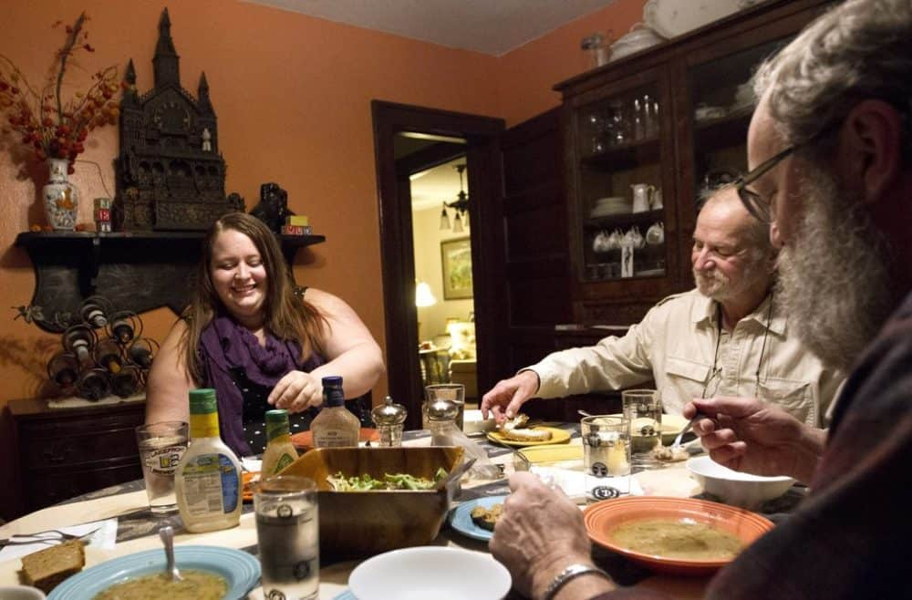 Sarah Fink, 24, left, has dinner with Mike, center, and Kim Muelbach at the Muelbachs' home in Minneapolis November 16, 2015.  When Sarah was 18 she moved in with the Muelbachs through the Avenues for Homeless Youth GLBT Host Home program. Sarah and the Muelbachs keep in touch, seeing each other every couple of months. (Courtney Perry for The Seattle Times)